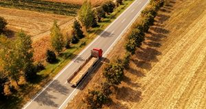 Truck on the road through countryside, aerial view