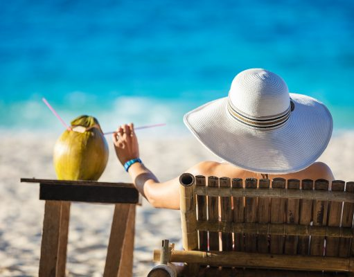 young-woman-sunbathing-and-drinking-coconut-juice